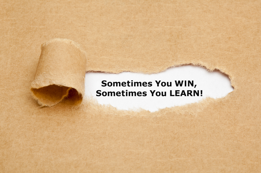 The text Sometimes You WIN Sometimes You LEARN, appearing behind torn brown paper. Motivational quote.